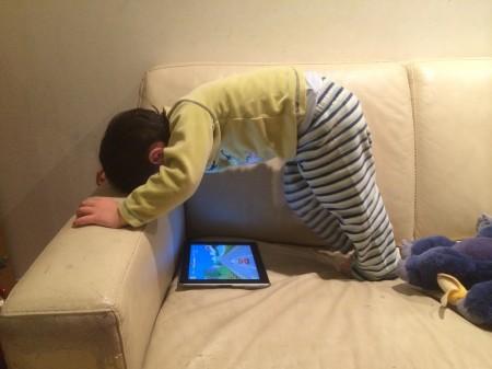 """Dans la série """"les poses improbables de Akira"""": jouer à un jeu video sur l'iPad."""